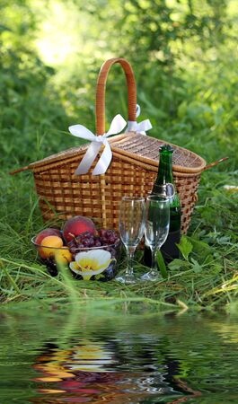 basket for picnic with champagne, fruits and reflection of it