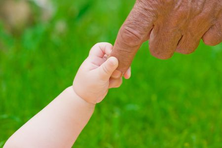 grandad's and baby's hands outdoors Banque d'images