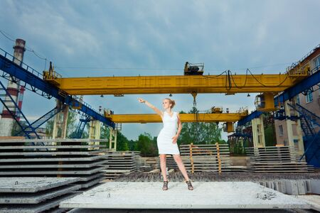 Young businesswoman posing over old factory photo