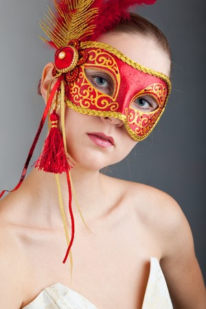 Portrait of attractive beautiful young woman wearing red carnival mask photo