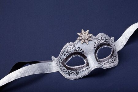 black and silver mask  on dark  background photo