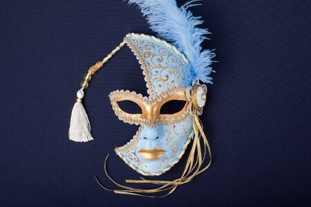blue and gold feathered mask isolated on a black background  photo