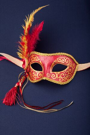 red and gold feathered mask on a dark background  photo