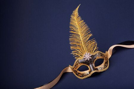 black and gold feathered mask on a dark background photo