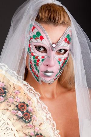 Portrait of beautiful young woman wearing carnival mask photo