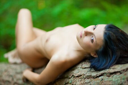 Perfect nude girl torso. Lie on tree in forest