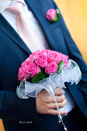 silver dress: groom hold wedding bouquet in hand Stock Photo