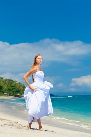 Bride walking along sea coast in the wedding dress