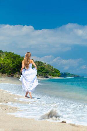 nude bride: Bride walking along sea coast in the wedding dress