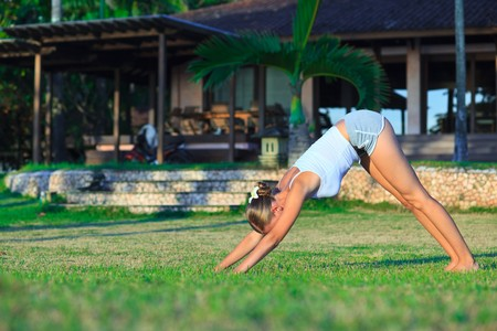 Beautiful young woman doing yoga exercise outdoors photo