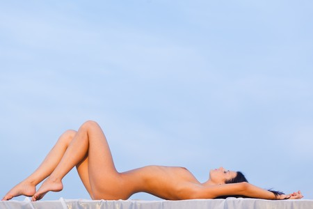 nude woman lie on the roof with white towel