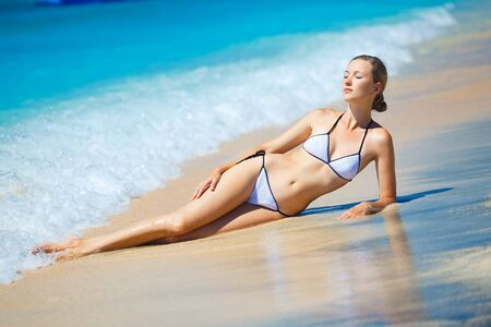 Bright photo of a beautiful model relaxing on a beach in Indonesia photo