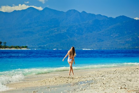 A beautiful woman wearing white bikini facing the sea on a vacant beach in paradise photo