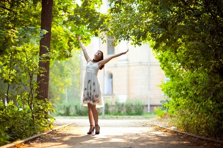 outstretched: Enjoying the nature. Young woman arms raised enjoying the fresh air in green forest. Stock Photo