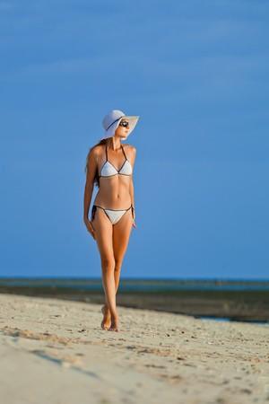 A beautiful woman wearing white bikini on a vacant beach in paradise photo