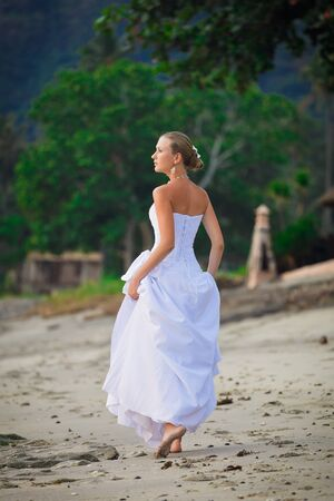 Bride walking along sea coast in the wedding dress photo