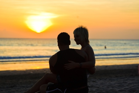 Two young lovers sitting on a beach and looking to each other on sunset background photo