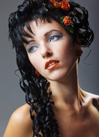 Beautiful face of a glamour woman with modern curly hairstyle and brightly makeup photo