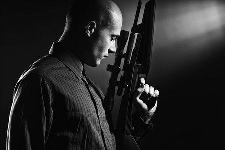 Portrait of a handsome young man holding a gun.