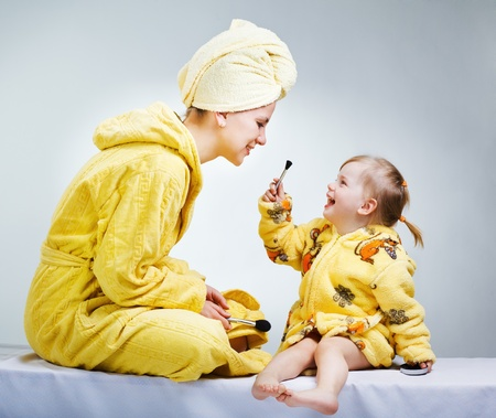 bathrobe: Daughter and mother putting makeup after bathroom
