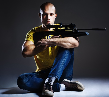 holding gun to head: dangerous sniper with the rifle