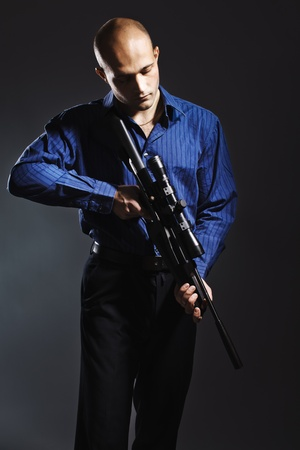 rifle: Portrait of a handsome young man holding a gun.