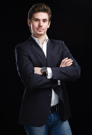 Fashion young businessman black suit on dark  background Stock Photo