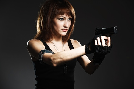 Sexy woman holding gun on gray photo