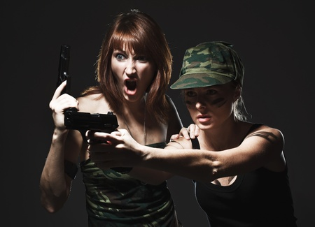 Sexy women holding gun on gray photo