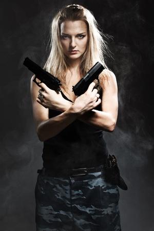 mujer con arma: Mujer atractiva la celebraci�n de arma de fuego con humo Foto de archivo
