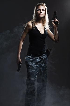 Sexy woman holding gun with smoke photo