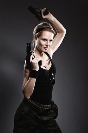 Sexy woman holding gun on gray
