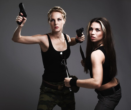 action shot: two sexy women with gun and dagger on gray