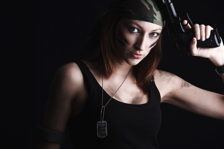 Sexy woman holding gun on dark photo
