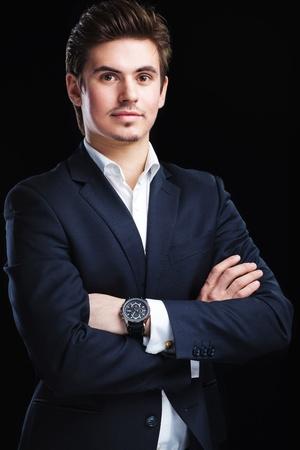 Fashion young businessman black suit on dark  background Banque d'images