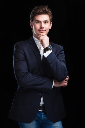 Fashion young businessman black suit on dark  background Archivio Fotografico