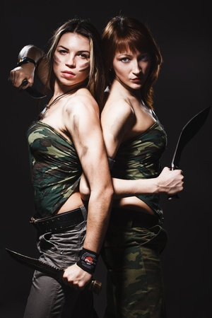 two sexy women with gun and dagger on gray photo