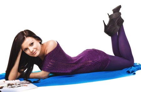 Happy cute beautiful  woman lying on the blue textile photo