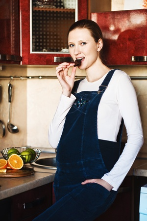 Pregnant woman in kitchen with  chocolate bar smiling photo