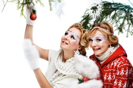 two girls holding christmas ball. Isolated photo