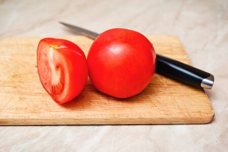 ripe tomato cut segment on board with knife photo