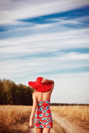 walk away: girl in red dress with red hat on the field. Rear view