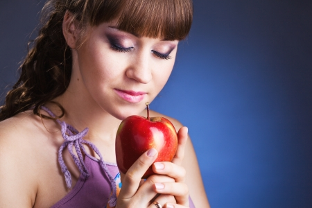 beautiful young woman with red apple, on blue background photo
