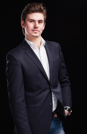 Fashion young businessman black suit on dark  background photo