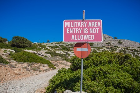 no surrender: military area no entry sign on blue sky Stock Photo