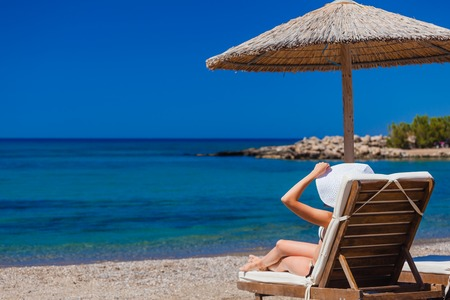 view of the beach with chairs and umbrellas. Greece Stock Photo