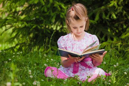 A little girl is  reading on the grass photo