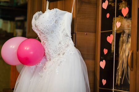 bodice: image of the bodice of a weeding dress on a hanger against a wooden revolving door