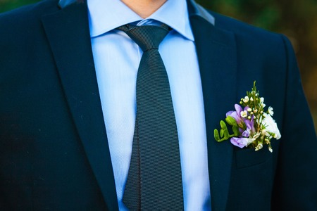 boutonniere: Groom with the boutonniere and tie