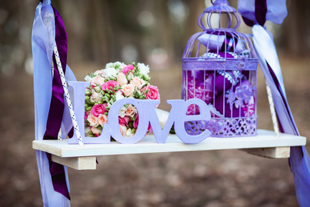Wedding decoration of a beautiful delicate bouquet lying down on a swing